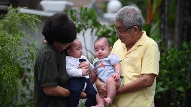 アジアの中国の先輩夫婦が、家の前庭で孫と遊んでいる - そっくりさん点の映像素材/bロール