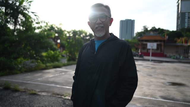 vidéos et rushes de un entraîneur chinois asiatique homme senior dans la matinée portant coupe-vent au terrain de basket-ball se préparant à la pratique et l'exercice - cadrage à la taille