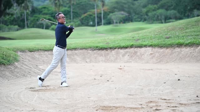 an asian chinese senior man golfer hitting his golf ball in a sand trap with his iron club - senior golf swing stock videos & royalty-free footage