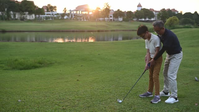 an asian chinese senior man golfer teaching his grandson how to play golf at golf course during sunset - golf shoe stock videos & royalty-free footage