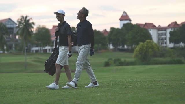 アジアの中国人男性ゴルファーが歩いて、メラカゴルフで楽しくゲームの終わりにゴルフバッグを運ぶ彼の息子と話しています - ゴルフシューズ点の映像素材/bロール