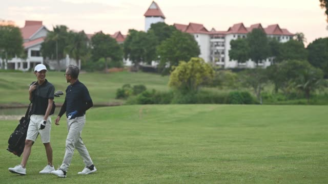 an asian chinese senior man golfer walking and talking to his son who carrying golf bag at the end of the game happily in melaka golf - golfer stock videos & royalty-free footage