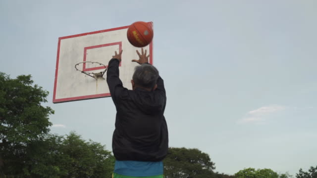 an asian chinese senior man practicing basket ball game in the basket ball court in the morning jumping making a shoot - shooting baskets stock videos & royalty-free footage