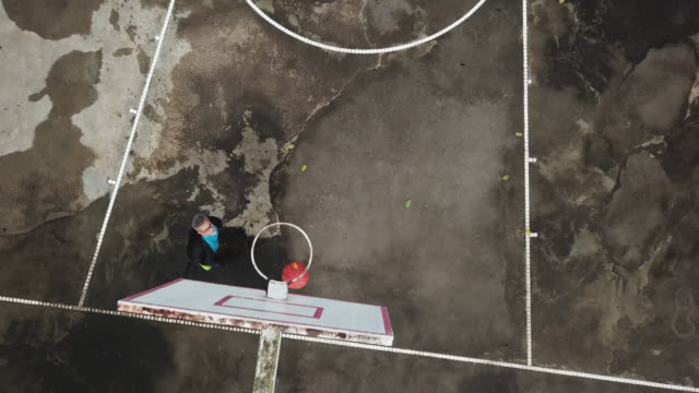 an asian chinese senior man practicing basket ball game in the basket ball court in the morning drone point of view - basket stock videos & royalty-free footage
