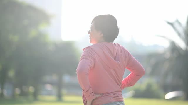 朝の公共公園で運動しているアジアの中国人先輩女性が、ウォームアップ運動をしている - 準備運動点の映像素材/bロール