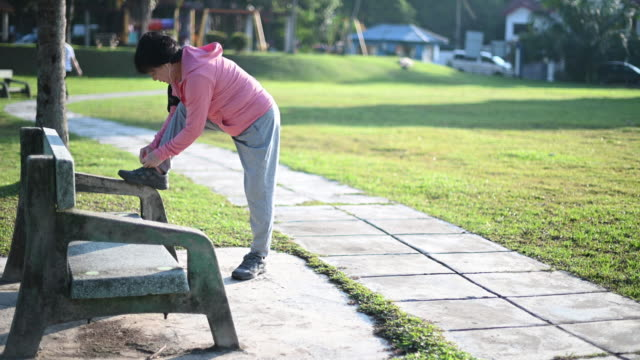 an asian chinese senior woman exercising in the public park in morning tying her shoes - malaysian ethnicity stock videos & royalty-free footage