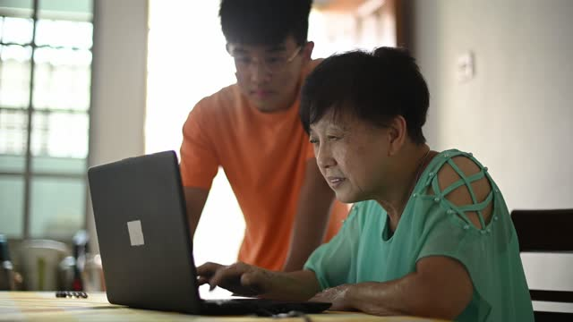 an asian chinese senior woman learning how to use laptop for social media from her grandson at dining room - dining room stock videos & royalty-free footage