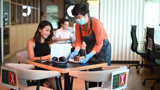 新しい通常として社会的な離散ソップ標準的な操作手順を練習しながら、テーブルで彼女の顧客のデザートを提供するアジアの中国の中小企業のカフェの所有者 - カフェ文化点の映像素材/bロール