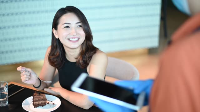 an asian chinese small business cafe owner woman talking to her customer for ordering in the cafe with new normal social distancing standard operating procedure - malaysian culture stock videos & royalty-free footage