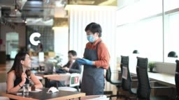 an asian chinese small business cafe owner woman talking to her customer for ordering in the cafe with new normal social distancing standard operating procedure