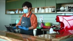 an asian chinese small business owner with face mask and protective gloves keying in check out payment