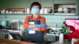 an asian chinese small business owner with face mask and protective gloves hand over the dessert to her customer at kitchen counter smiling looking at camera