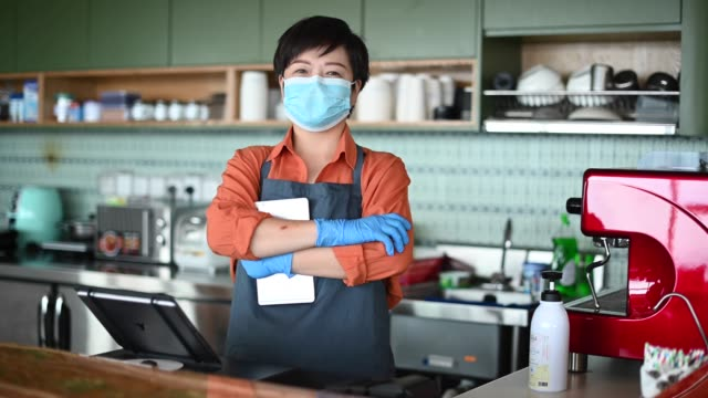 an asian chinese small business owner with face mask and protective gloves hand over the dessert to her customer at kitchen counter smiling looking at camera - south east asian ethnicity stock videos & royalty-free footage
