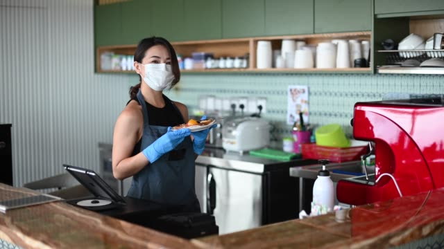 an asian chinese small business owner with face mask and protective gloves hand over the dessert to her customer at kitchen counter smiling looking at camera - glove video stock e b–roll