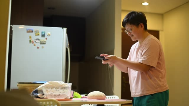 an asian chinese stay home mother preparing dough and taking photo using her phone - home made stock videos & royalty-free footage