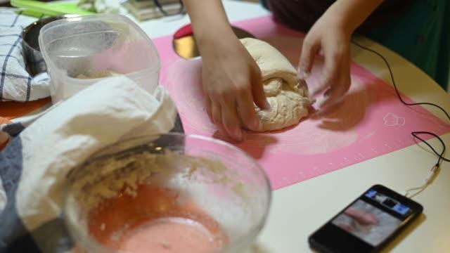 una madre asiatica cinese rimanere a casa preparando pasta mentre si utilizza il telefono online controllare per la ricetta e la guida lezione online - ricetta video stock e b–roll