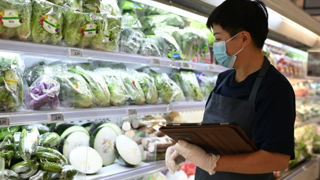 an asian chinese supermarket shopkeeper retail assistant with face mask - greengrocer stock videos & royalty-free footage