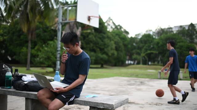 vidéos et rushes de un adolescent chinois asiatique faisant des devoirs utilisant l'ordinateur portatif au banc public de parc tandis que ses amis jouant la boule de panier - malaysian culture