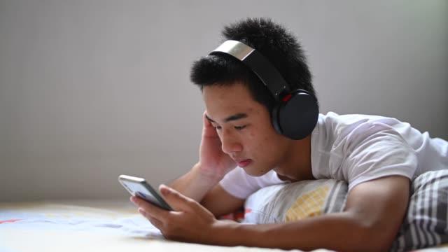 en asiatisk kinesisk tonåring pojke hemma lyssnar på musik med sina hörlurar under helgen ligger på sängen - 16 17 år bildbanksvideor och videomaterial från bakom kulisserna