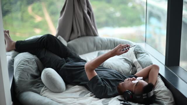 stockvideo's en b-roll-footage met een aziatische chinese tienerjongen die aan muziek met zijn hoofdtelefoon en zijn slimme telefoon luistert die op kussen ligt - alleen één tienerjongen