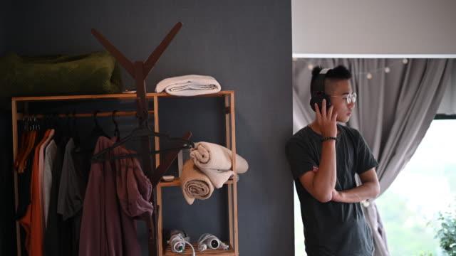 stockvideo's en b-roll-footage met een aziatische chinese tienerjongen die aan muziek met zijn hoofdtelefoon luistert die weg kijkt - alleen één tienerjongen