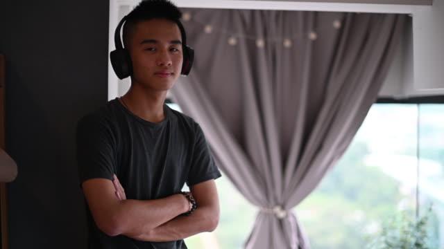 stockvideo's en b-roll-footage met een aziatische chinese tienerjongen die aan muziek met zijn hoofdtelefoon luistert die camerawapen bekijkt gekruist - alleen één tienerjongen