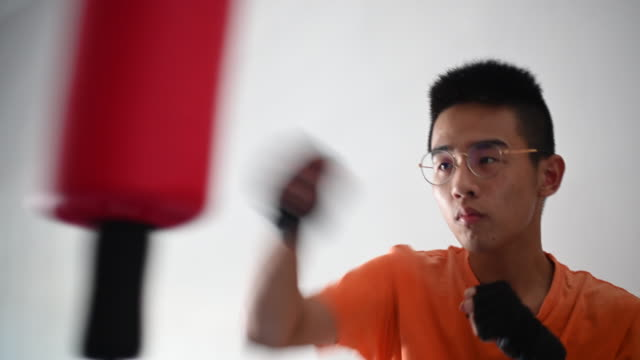 an asian chinese teenager boy practising boxing in his bedroom during coronavirus quarantined period - martial arts stock videos & royalty-free footage