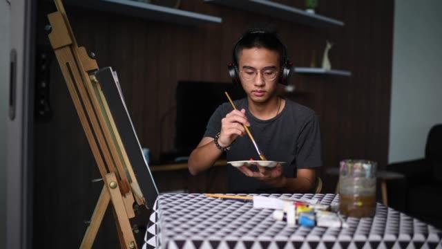 vidéos et rushes de un adolescent chinois asiatique dessinant la peinture acrylique à la maison dans le salon - métier d'art
