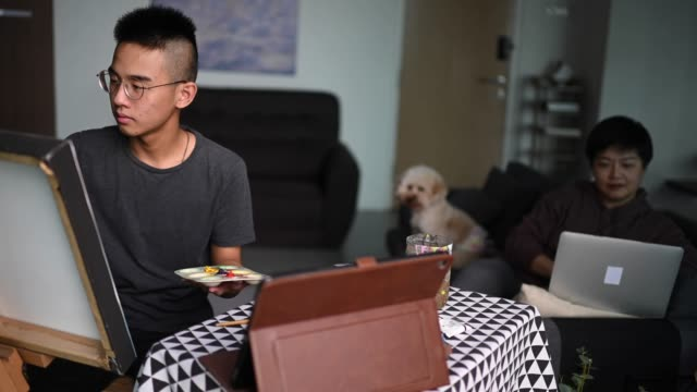 an asian chinese teenager drawing acrylic painting at home in living room using tablet e learning online while his mother working using laptop on sofa with pet toy poodle - teenagers only stock videos & royalty-free footage
