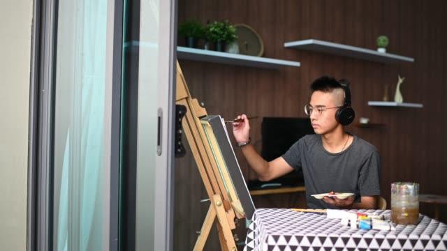 vidéos et rushes de un adolescent chinois asiatique dessinant la peinture acrylique à la maison dans le salon - 16 17 ans
