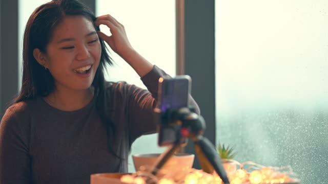 vídeos de stock, filmes e b-roll de uma adolescente asiática chinesa vlogging em seu quarto comendo maçã usando seu telefone inteligente durante o dia de chuva sorrindo - só uma adolescente menina