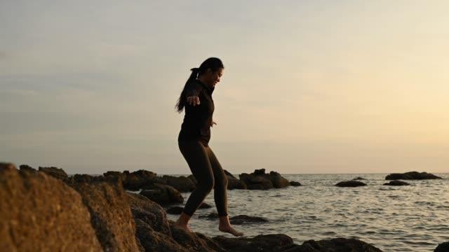 en asiatisk kinesisk tonåring går ner till stranden med stenar försiktigt - endast en tonårsflicka bildbanksvideor och videomaterial från bakom kulisserna