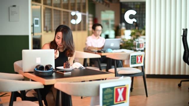 カフェで休憩を取って彼女のデザートを楽しんでいるアジアの中国のホワイトカラー労働者 - white collar worker点の映像素材/bロール