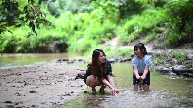 an asian chinese woman having bonding tine with her daughter at the river playing with water splashing - chinese ethnicity stock videos & royalty-free footage