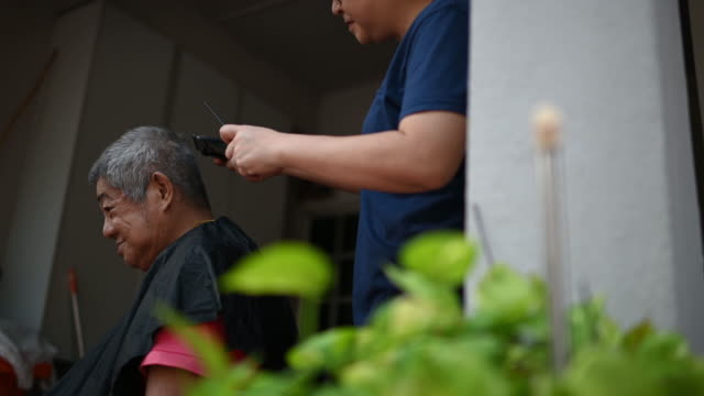an asian chinese woman is cutting and trimming her father's hair at front yard of her house during the quarantine period of coronavirus - cutting hair stock videos & royalty-free footage
