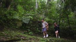 an asian chinese woman leading her son for jungle trekking in the morning climbing down