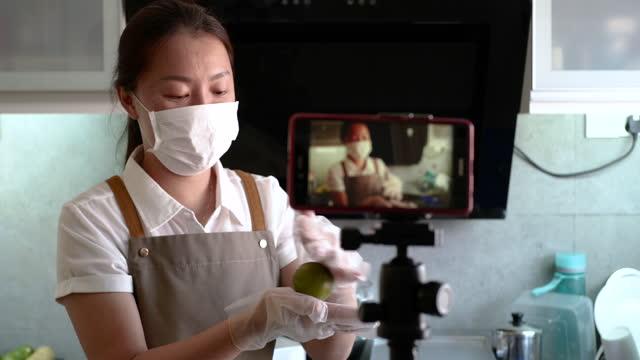 stockvideo's en b-roll-footage met een aziatische chinese vrouw die vlog voor het bakken tutorial registreert - tutorial