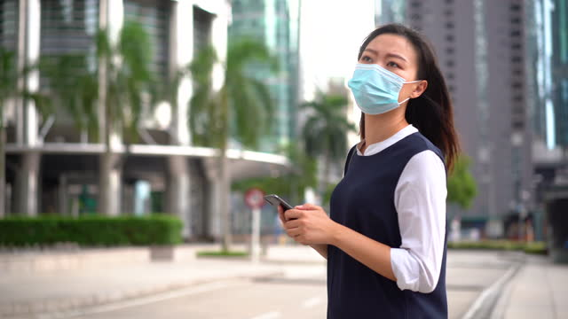 an asian chinese woman wearing protective face mask and using smartphone - petronas twin towers stock videos & royalty-free footage
