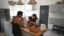 An asian chinese young family father mother and their daughter having snack in the kitchen eating homemade bread enjoying