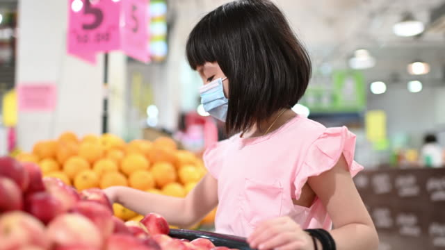 an asian chinese young girl buying fruit in supermarket duriing weekend looking at the fruit peach - south east asian ethnicity stock videos & royalty-free footage