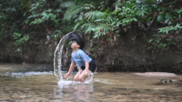 an asian chinese young girl having fun in the river playing with water swinging her hair backward