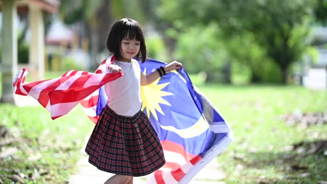 an asian chinese young girl wrapped in malaysia national flag turning around in public park - cultura malesiana video stock e b–roll