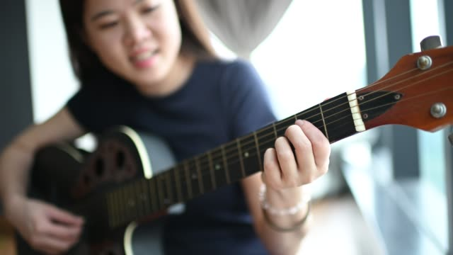 an asian chinese young lady playing guitar at home during leisure time hobby happily - day in the life stock videos & royalty-free footage