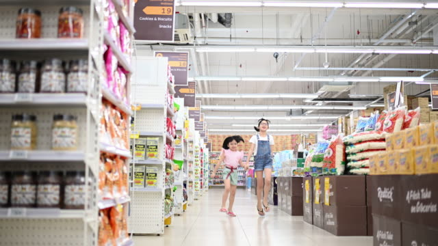 an asian chinese young sisters siblings standing in front of the camera inside supermarket - convenienza video stock e b–roll