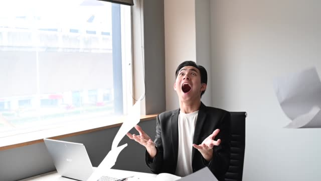 an asian chinese young white collar worker throwing papers in the air frustrated and emotional stress in his office sitting on his chair - frustration asian failure stock videos & royalty-free footage
