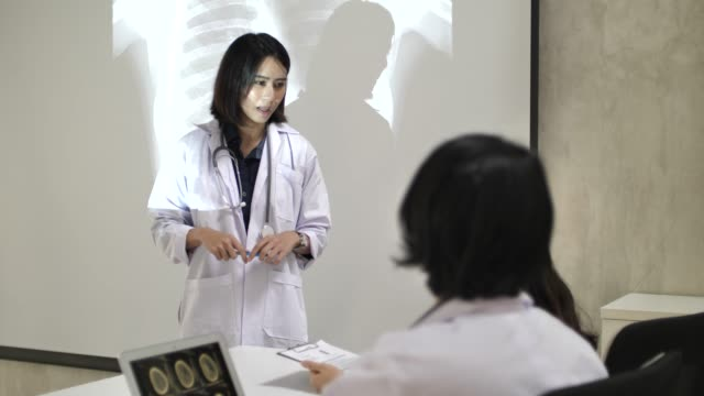 an asian doctor giving a presentation on x-ray image with doctor team - female doctor stock videos & royalty-free footage