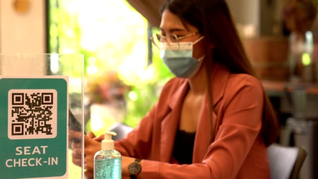an asian employee wearing a surgical mask working with mobile phone in the coffee shop - distant stock videos & royalty-free footage