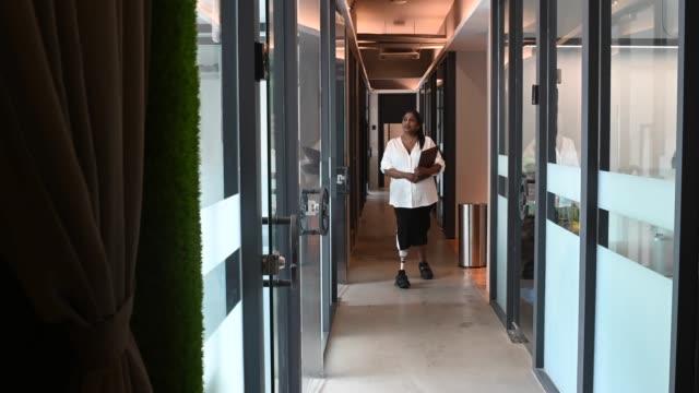 vídeos de stock, filmes e b-roll de uma mulher indiana asiática trabalhadora de colarinho branco deficiente com membro protético segurando seu tablet digital e andando no corredor do escritório sorrindo - disability