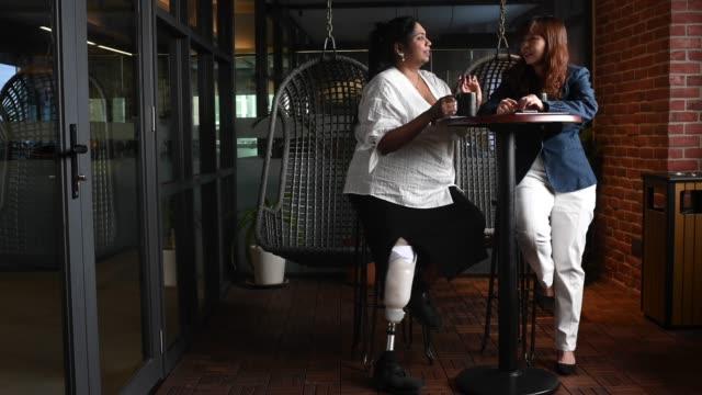 彼女のアジアの中国の女性の同僚の株式とコーヒーブレイクを持つ義足を持つアジアのインドの女性ホワイトカラー労働者 - white collar worker点の映像素材/bロール