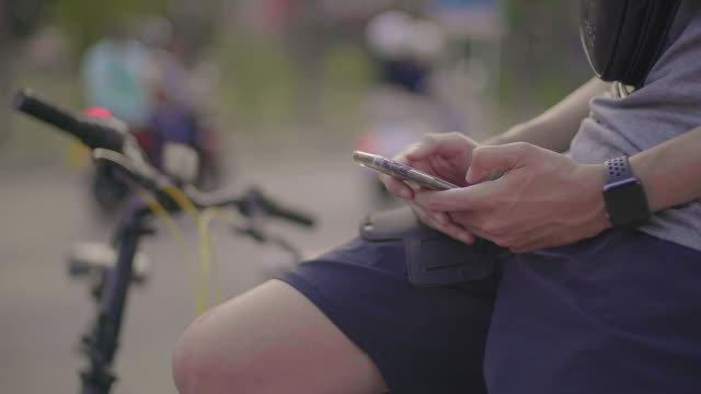 an asian man is sitting on a mobile phone after riding a bicycle. - chairperson stock videos & royalty-free footage